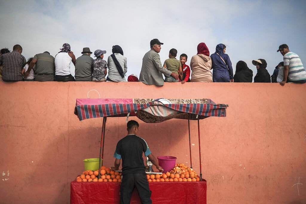A vendor sells orange juice as people sit on a fence to watch a horsemanship show known as Fantasia or Tabourida, in the coastal town of El Jadida, Morocco. (AP Photo/Mosa'ab Elshamy)