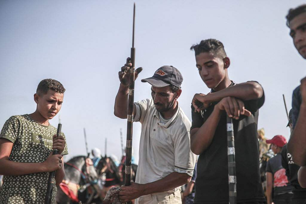 A man helps prepare rifles before being loaded with gunpowder to be used in Tabourida, a horse riding show also known as Fantasia, in the town of El Jadida, Morocco. (AP Photo/Mosa'ab Elshamy)