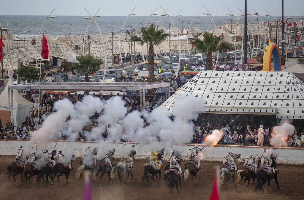 A troupe charges and fires their rifles during Tabourida, a traditional horse riding show also known as Fantasia, in the coastal town of El Jadida, Morocco. (AP Photo/Mosa'ab Elshamy)
