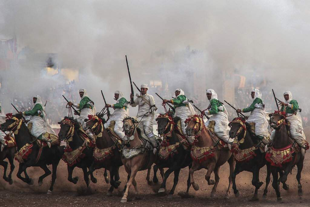 A troupe charges firing their rifles during Tabourida, a traditional horse riding show also known as Fantasia, in the coastal town of El Jadida, Morocco. (AP Photo/Mosa'ab Elshamy)