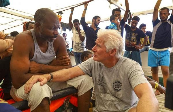 Actor Richard Gere talks with migrants aboard the Open Arms Spanish humanitarian boat, which has been carrying 121 migrants for a week in the central Mediterranean. (AP Photo/Valerio Nicolosi)
