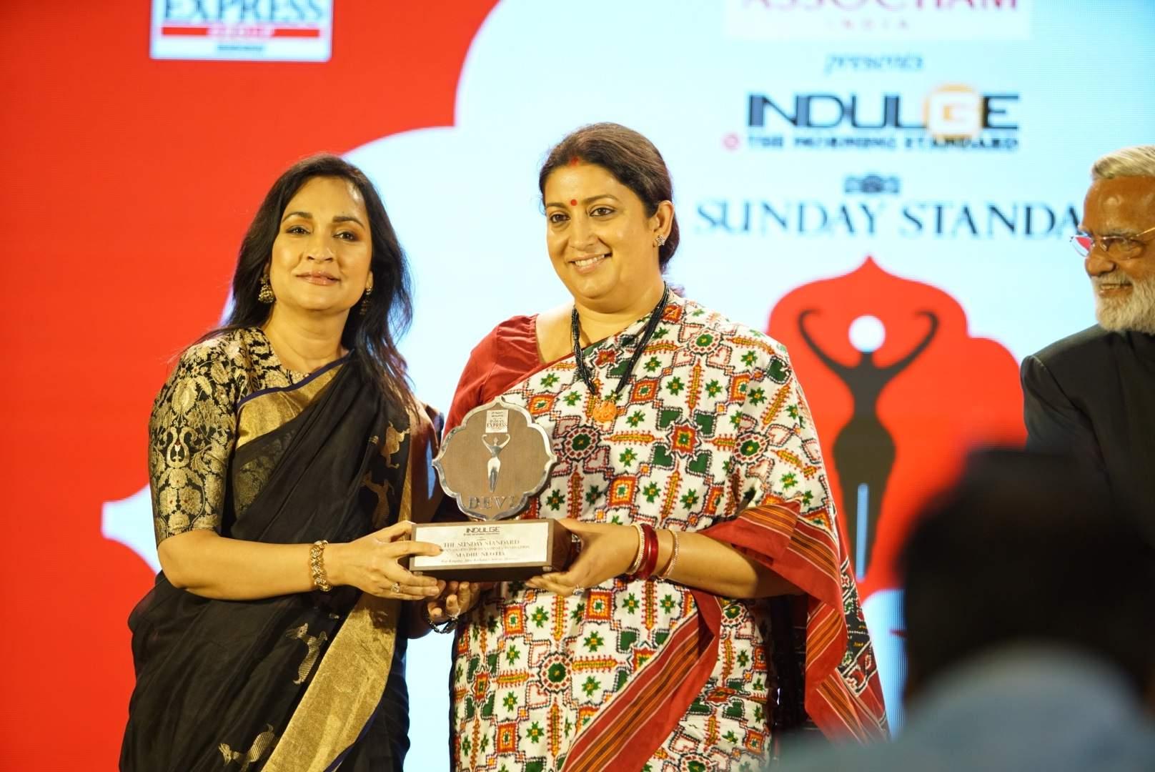 The honourable minister Smriti Irani hands over the award to sartorial visionary Madhu Neotia