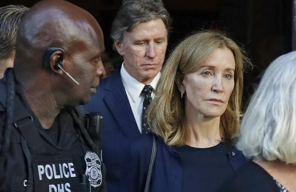 Felicity Huffman leaves federal court with her husband William H Macy and her brother Moore Huffman Jr. after she was sentenced in Boston. (AP Photo/Michael Dwyer)