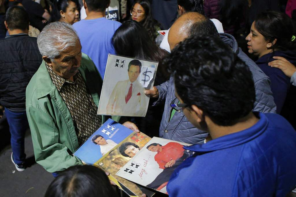 A vendor sells records by Jose Jose to fans who gathered to mourn his death at Jose Jose's statue in Mexico City. Jose Jose, known as the 'Prince of Song,' has died at age 71. (AP Photo/Anthony Vazque