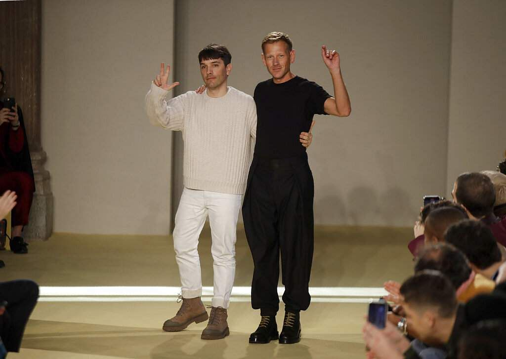 Creative director Paul Andrew accepts applause flanked by menswear designer Guillaume Meilland at the Salvatore Ferragamo men's Fall-Winter 2020/21 fashion show in Milan, Italy. (AP Photo/Luca Bruno)
