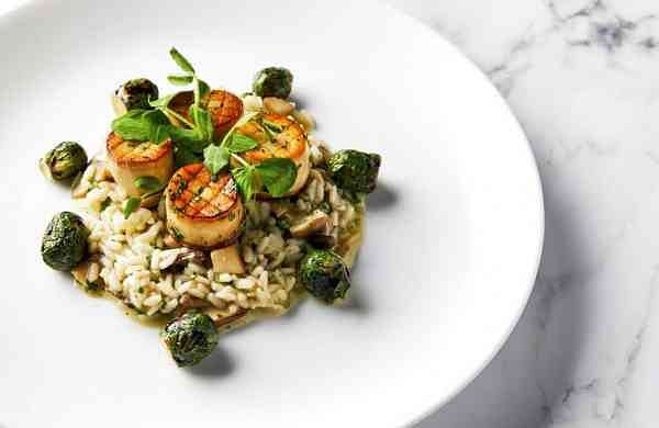 King oyster mushroom scallops on a bed of wild mushroom risotto with roasted Brussels sprouts by Beverly Hilton Executive Chef Matthew Morgan (Leslie Grow/Golden Globe Awards via AP)
