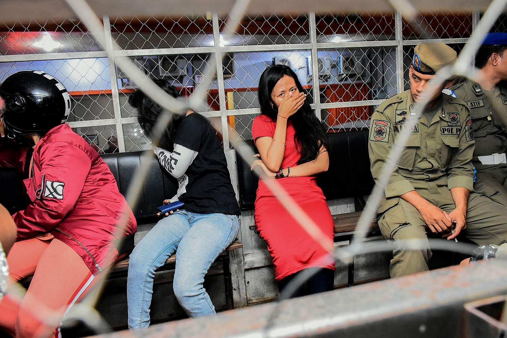 Women detained during a raid in Makassar (AFP/Indra Abriyanto)