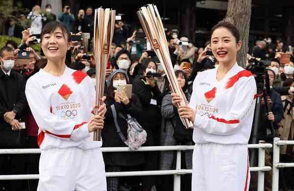 A torchbearer and Satomi Ishihara with the Olympic torch (AFP / JIJI PRESS / STR)