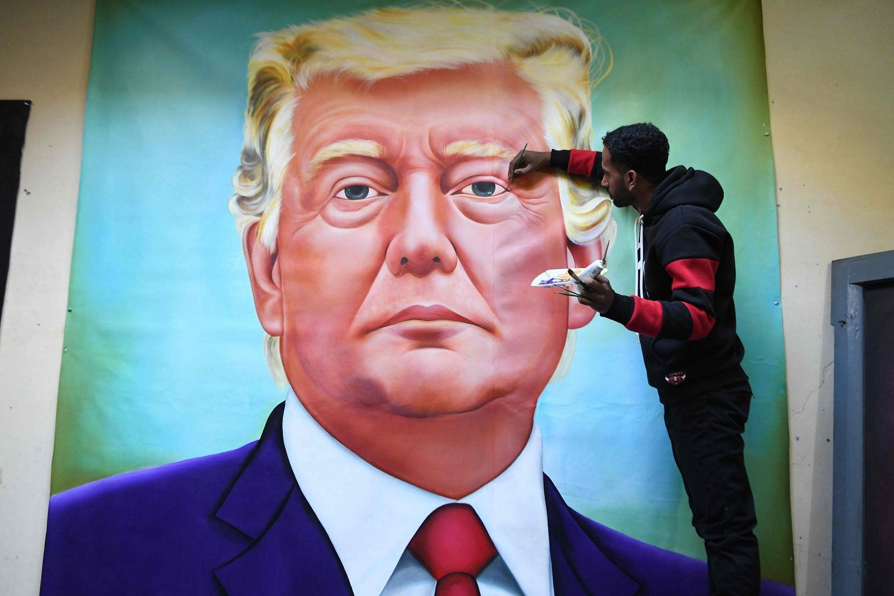 Amritsar, Punjab: Painter Jagjot Singh Rubal gives final touches to a painting of Donald Trump, days before the US President and his wife Melania are scheduled to arrive in India. (AFP/Narinder Nanu)