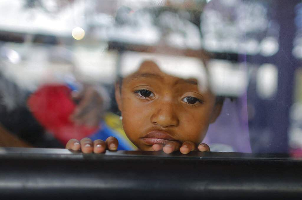 A girl looks out of a bus window in Caracas. The debate over fresh US sanctions aimed to force out Venezuela's Nicolás Maduro is playing out in the crisis-stricken nation. (AP Photo/Ariana Cubillos)