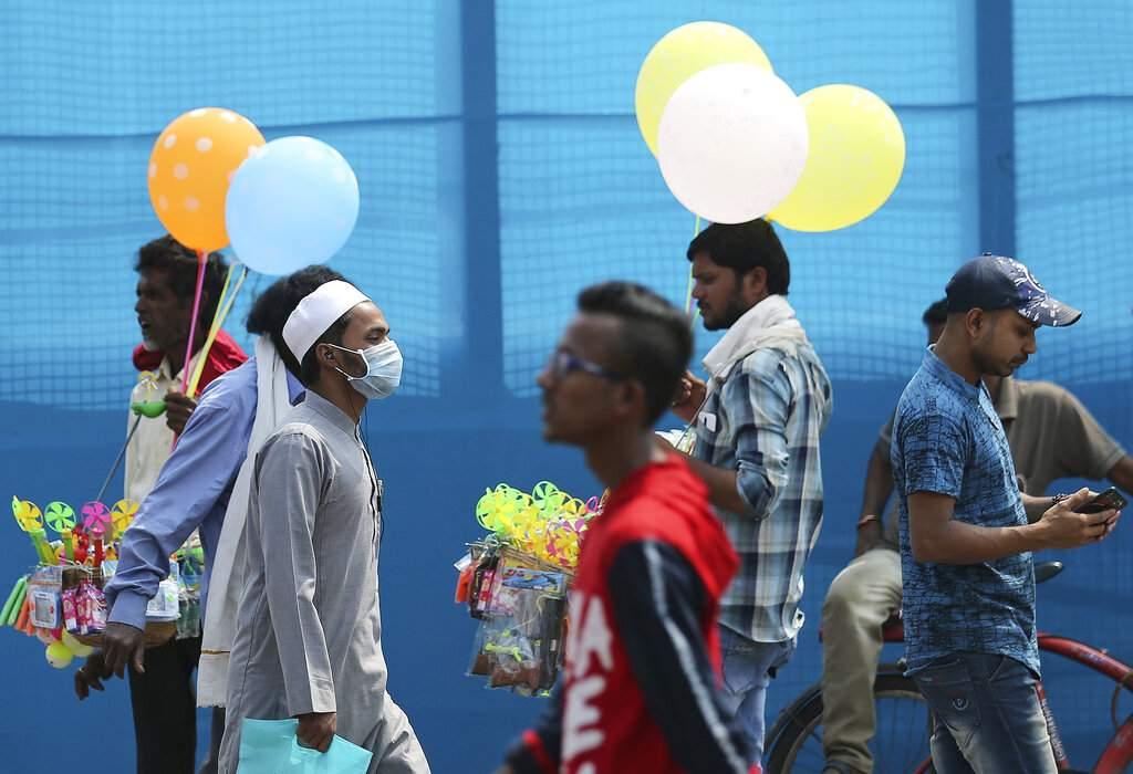 A man wearing a mask is seen walking on a street in Hyderabad, India. (AP Photo/Mahesh Kumar A)