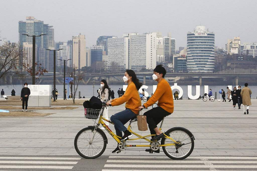 A couple wearing face masks rides a bicycle at a park in Seoul, South Korea. (AP Photo/Ahn Young-joon)