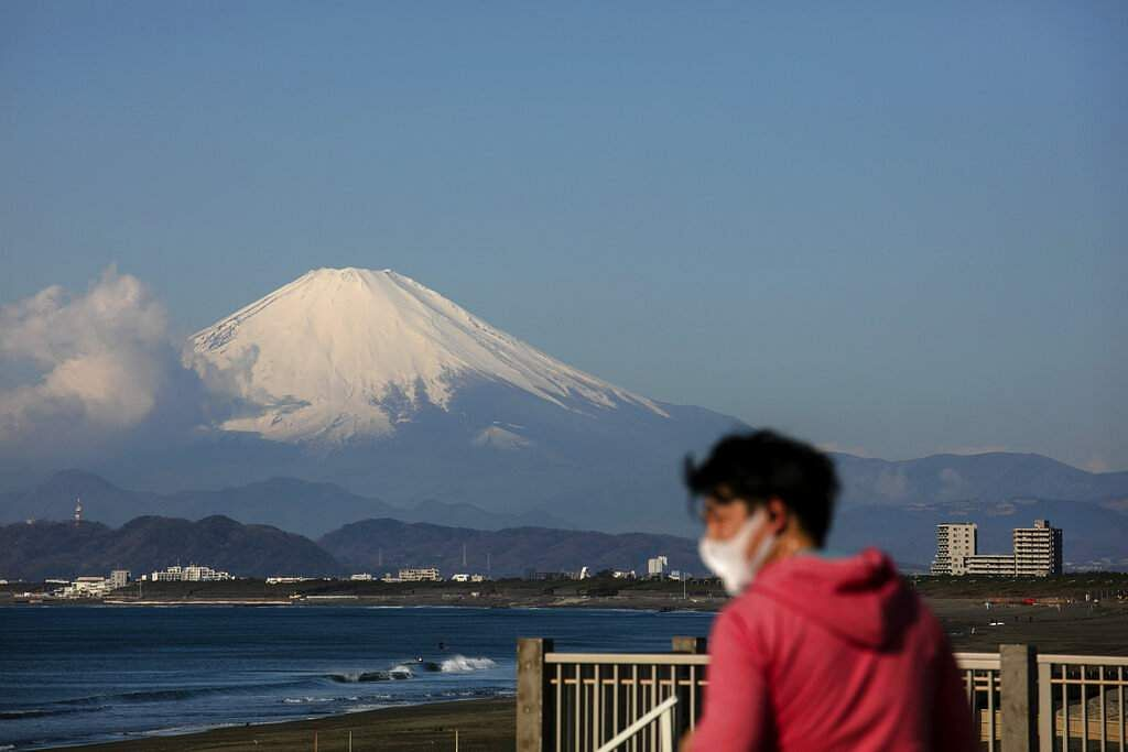 A man wearing a mask visits a beach as snow-capped Mount Fuji is visible in the distance in Fujisawa, Japan. (AP Photo/Jae C Hong/File)