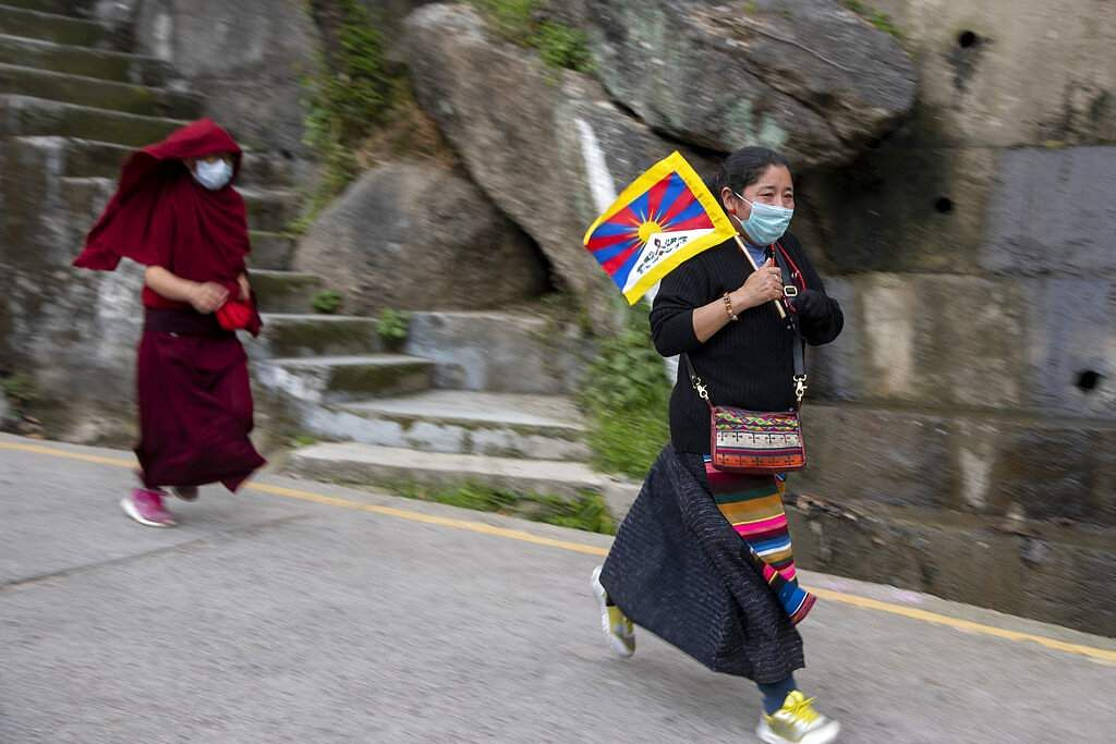 An exiled Tibetan wears a protective mask during a protest march marking the anniversary of the 1959 Tibetan uprising in Lhasa, as Tibetans gather in Dharamshala. (AP Photo/Ashwini Bhatia)