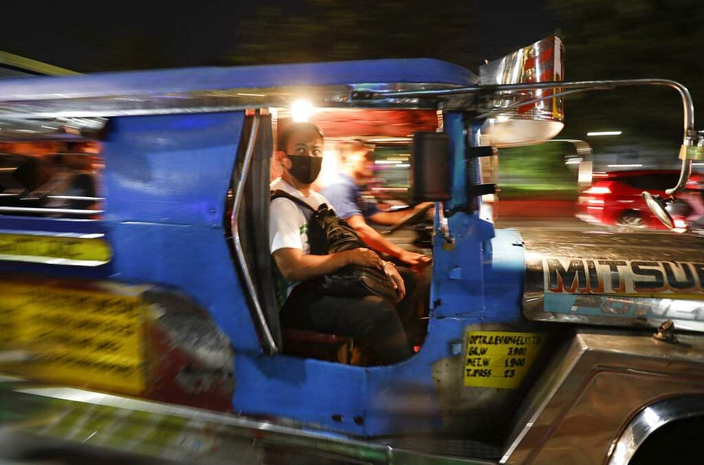 A man wears a protective mask as he rides a passenger jeepney in Manila, Philippines. (AP Photo/Aaron Favila)