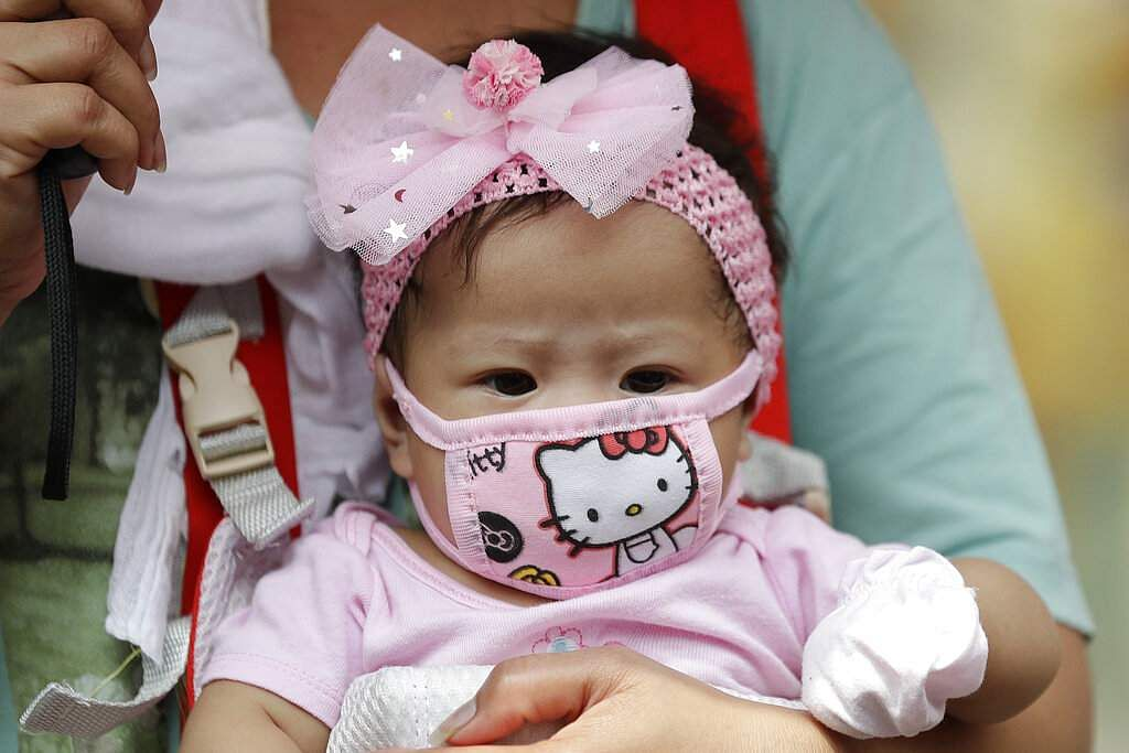 A baby wears a protective mask in Manila, Philippines. (AP Photo/Aaron Favila)