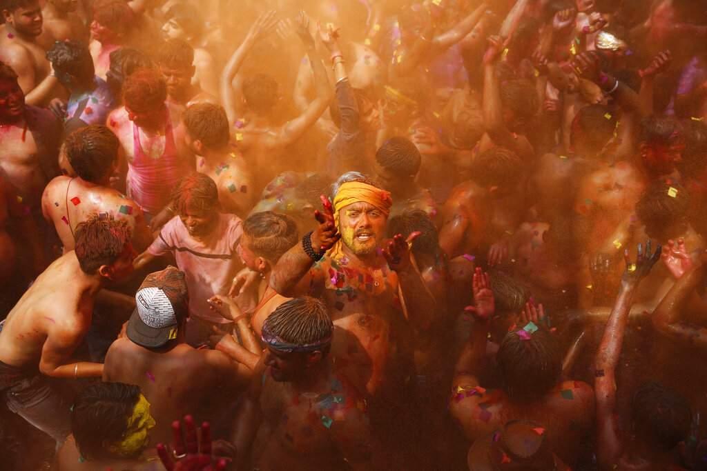 Revelers dance during Holi celebrations, the Hindu festival of colours in Prayagraj, India. (AP Photo/Rajesh Kumar Singh)