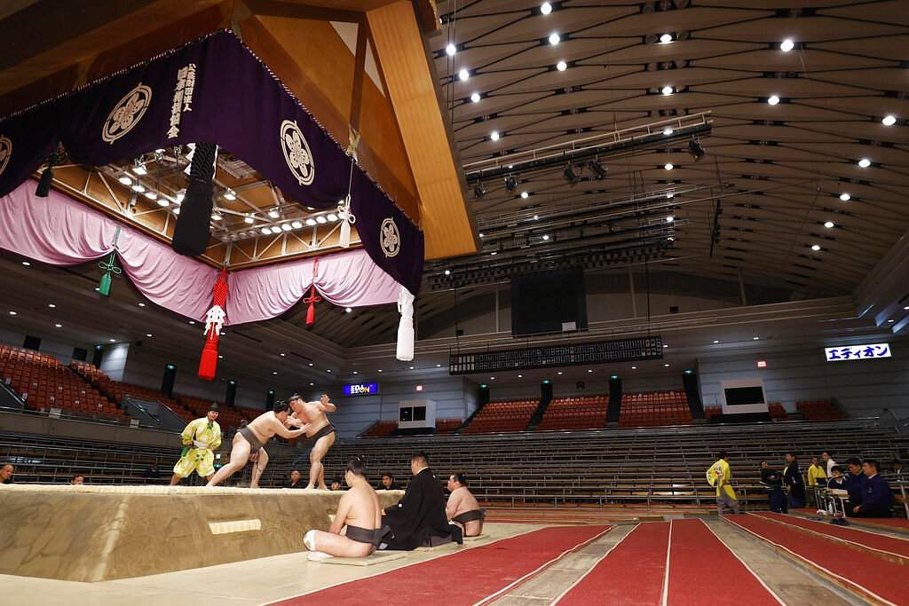 Sumo wrestlers fight on the ring as spectators' seats are empty during the Spring Grand Sumo Tournament in Osaka, western Japan. (Kyodo News via AP)
