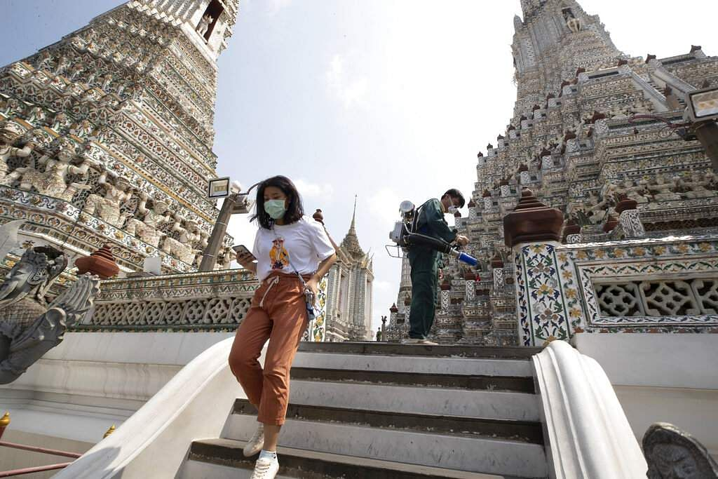 A tourist wearing a protective mask walks by a worker spraying disinfectant at the Temple of Dawn in Bangkok, Thailand. (AP Photo/Sakchai Lalit)