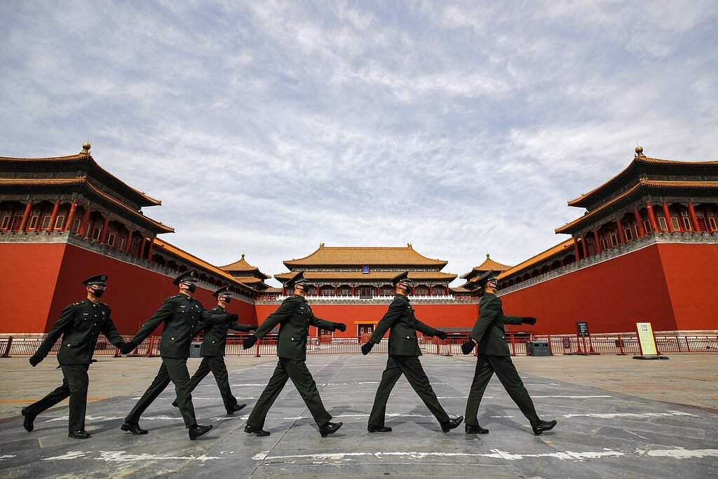 Soldiers wearing face masks march past the closed entrance gates to the Forbidden City in Beijing. (AP Photo/Andy Wong)