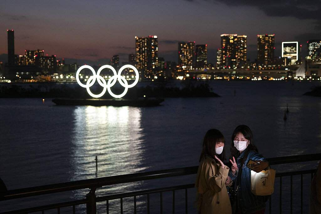 Two women take a selfie with the Olympic rings in the background in the Odaiba section of Tokyo, Japan. (AP Photo/Jae C Hong)