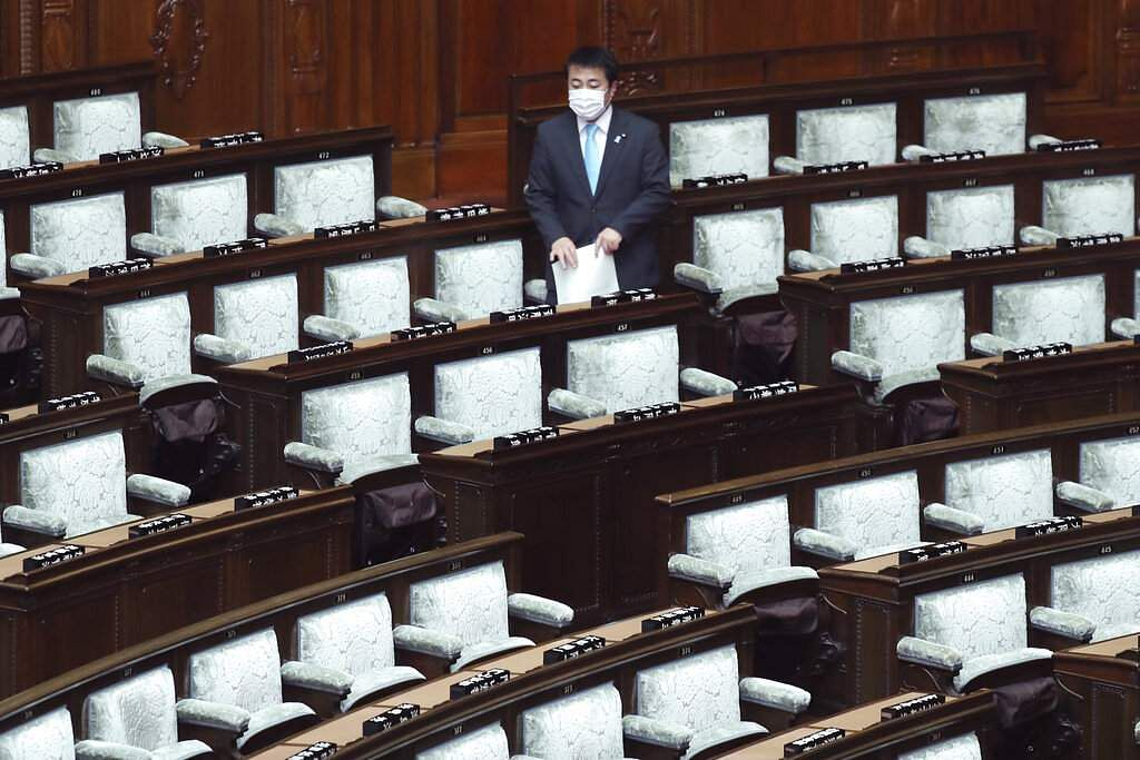 A lawmaker wearing a face mask arrives for a plenary session at the lower house of parliament in Tokyo, Japan. (AP Photo/Koji Sasahara)