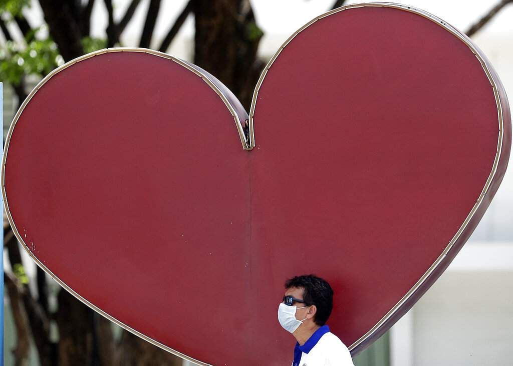 A man wearing a protective mask stands behind a heart-shaped logo in Marikina, east of Manila, Philippines. (AP Photo/Aaron Favila)
