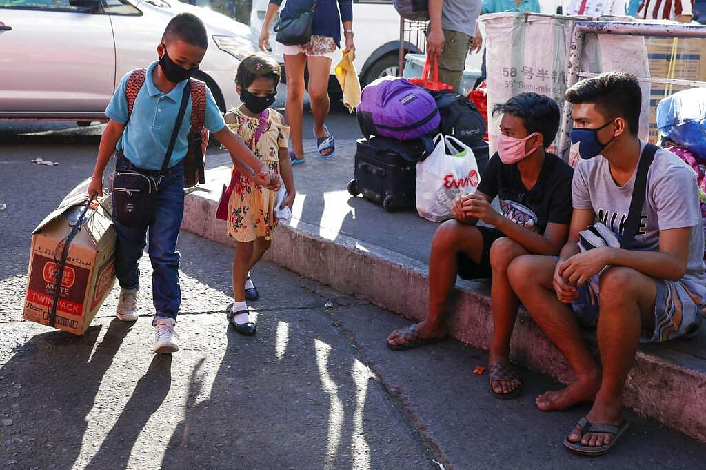 A young boy and girl hold hands as they arrive with their parents to try to catch a ride at the Cubao bus terminal in Manila, Philippines. (AP Photo/Aaron Favila)