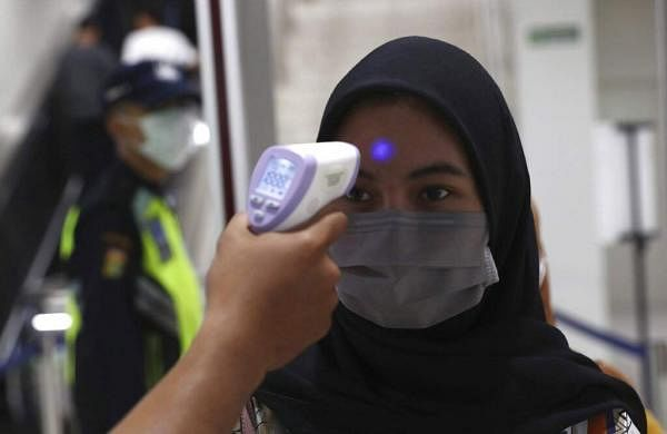 A medical team member checks a passenger's body temperature at a Mass Rapid Transit (MRT) station in Jakarta, Indonesia. (AP Photo/Tatan Syuflana)