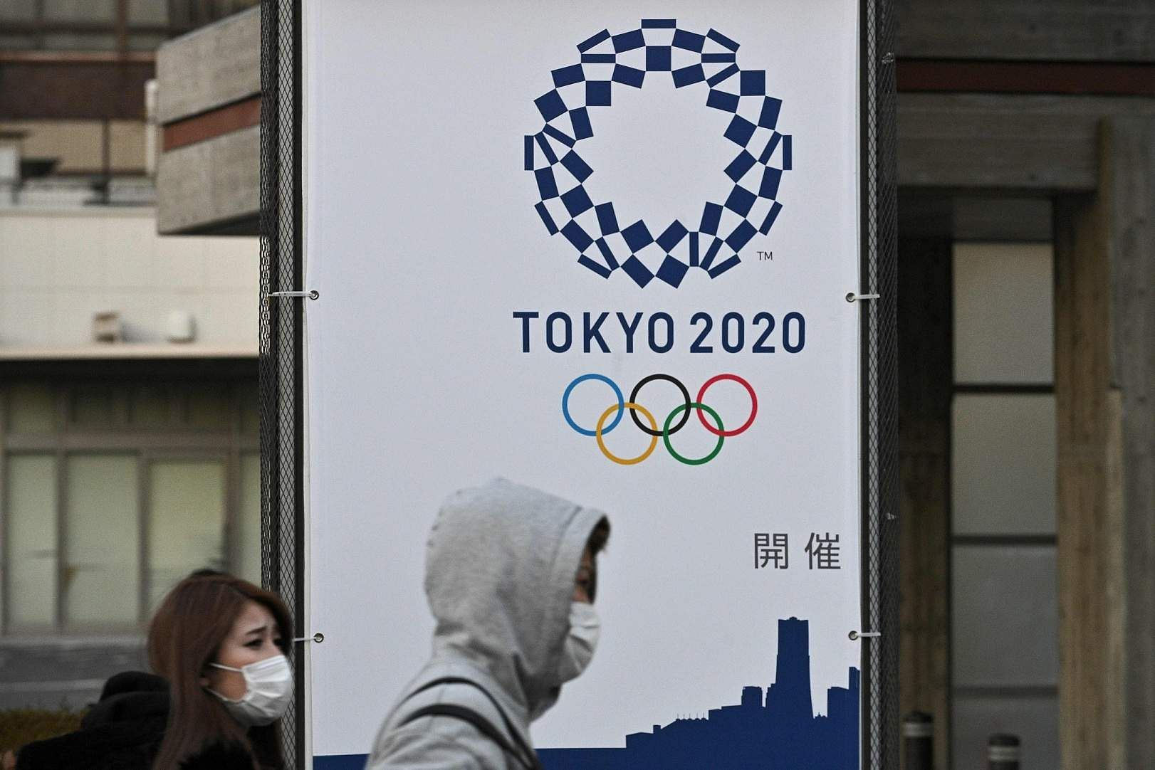 Yokohama, Kanagawa Prefecture, Japan: Pedestrians wearing face masks walk past a board showing the number of days to the Tokyo 2020 Olympic Games. (AFP/Philip FONG)