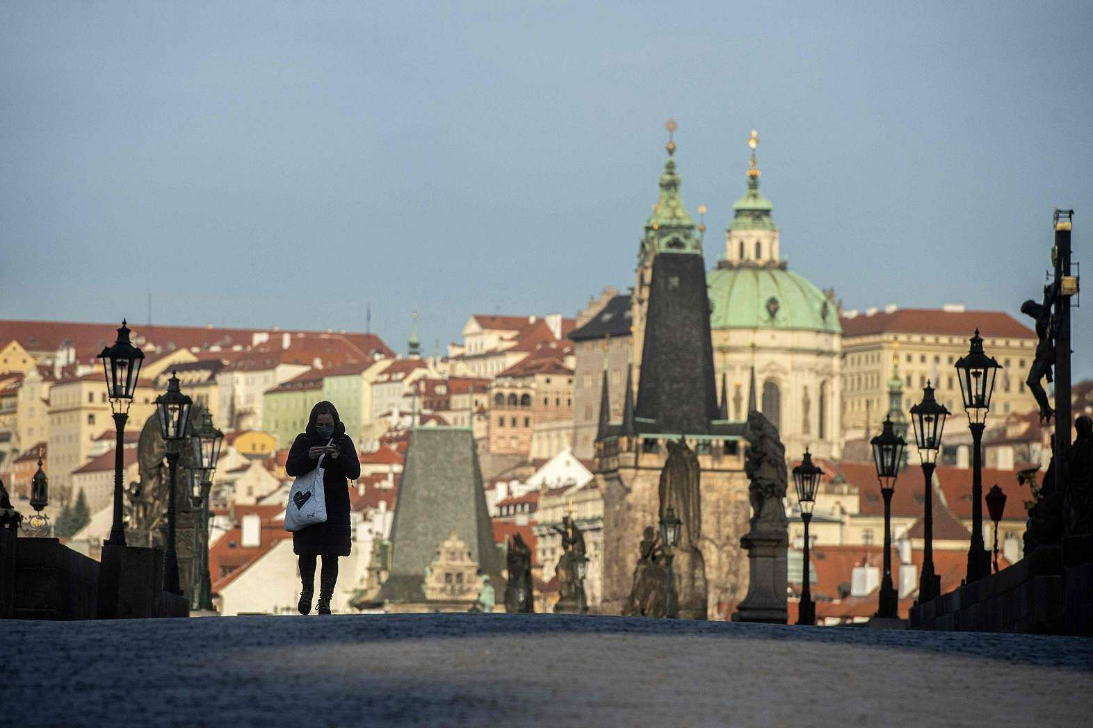 Prague: A woman wearing a protective mask walks across an empty Charles Bridge. The Czech govt has imposed restrictions on movement to combat the coronavirus. (AFP/Michal Cizek)