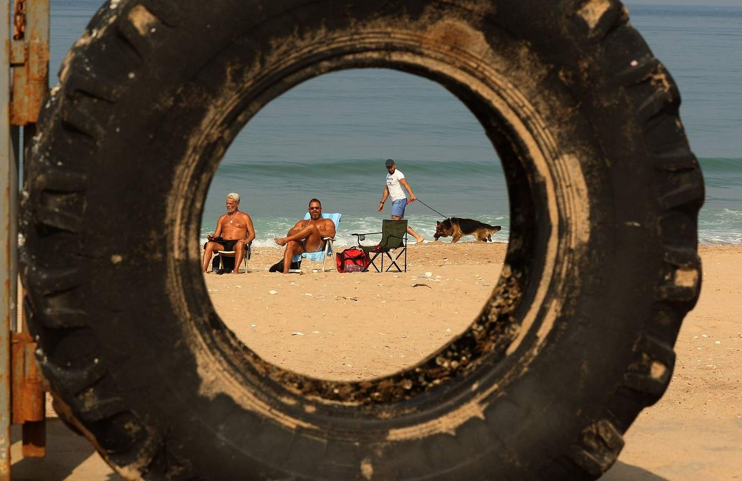 Sidon, Lebanon: People gather on the beach in the southern Lebanese city of Sidon. People were urged to stay at home for two weeks to stem the novel coronavirus outbreak. (AFP/Mahmoud ZAYYAT)