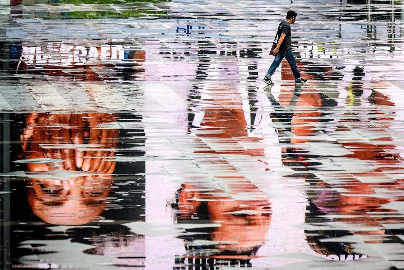 Bangkok: A man wearing a face mask, amid concerns over the spread of the coronavirus, walks between puddles reflecting advertisement screens on an empty square in Bangkok. (AFP/Mladen ANTONOV)