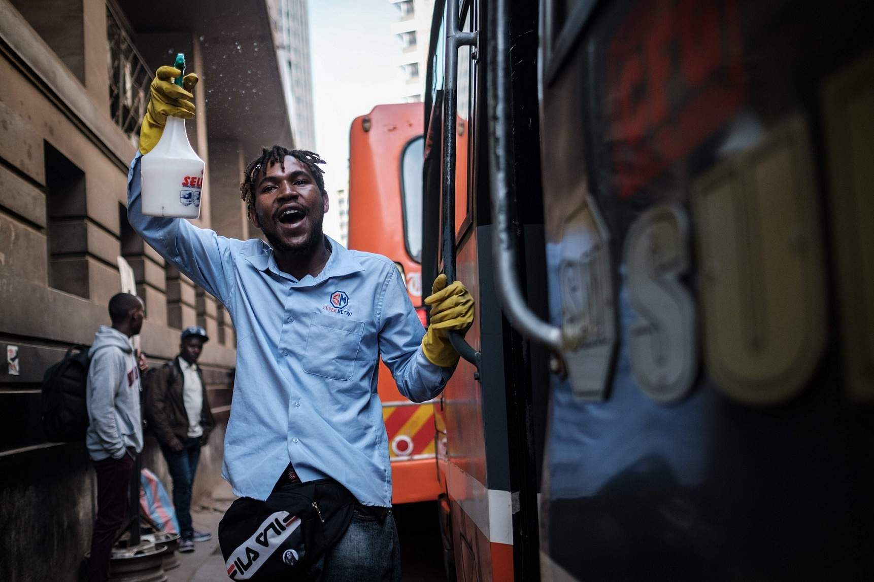 Nairobi, Kenya: A staff member of Matatu, a privately owned minibus, shouts destinations of where the minibus will stop as he provides hand disinfectant to passengers. (AFP/Yasuyoshi CHIBA)