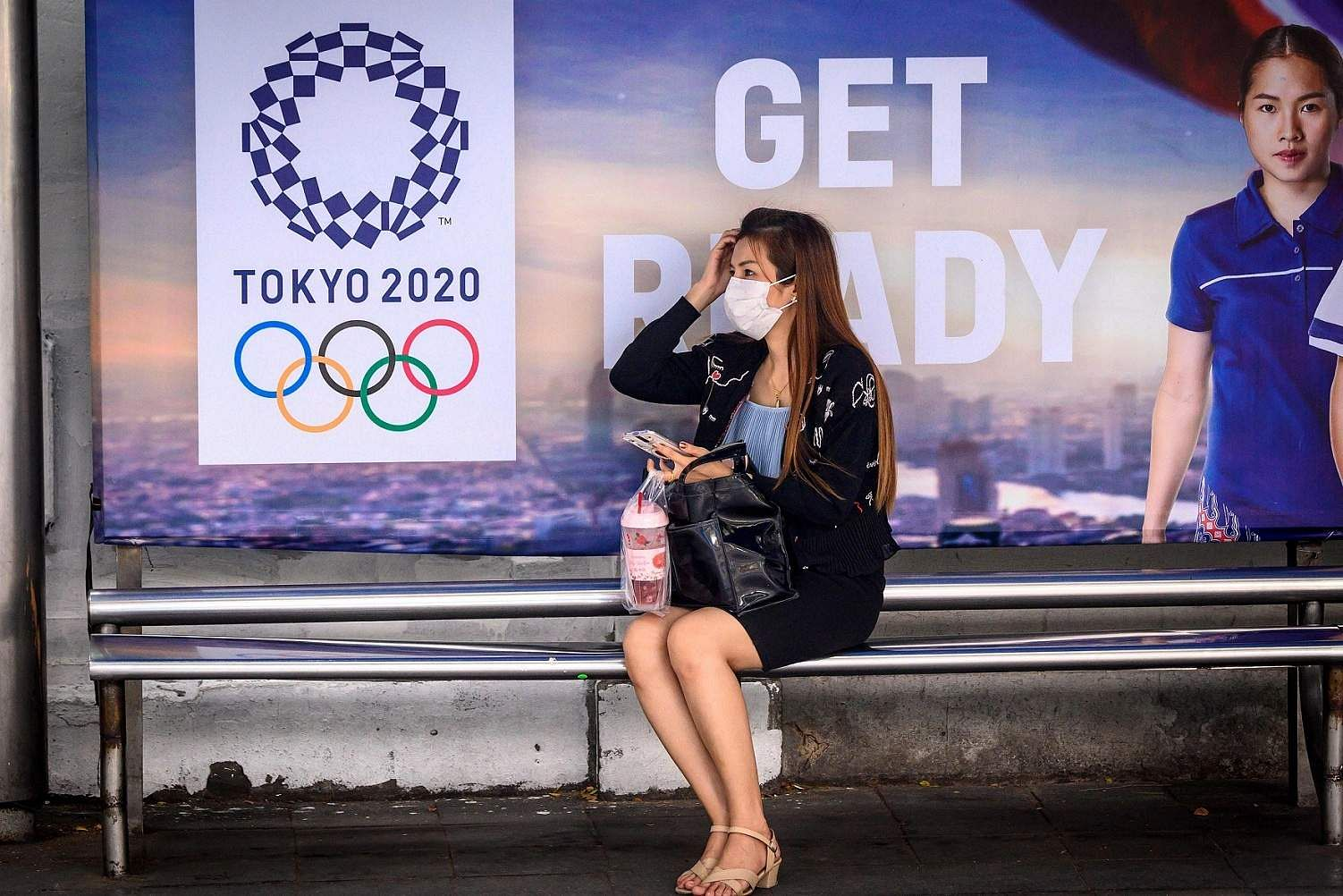 Bangkok, Thailand: A woman wearing a face mask, amid concerns over the spread of the coronavirus, sits at a bus stop in front of a Tokyo 2020 Olympics advertisement. (AFP/Mladen ANTONOV)