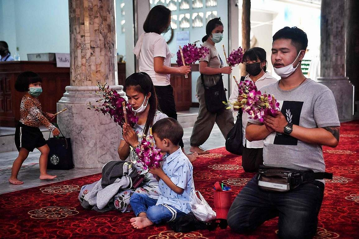Bangkok, Thailand : Devotees wear face masks amid concerns over the spread of the coronavirus while praying at Wat Pak Nam Buddhist temple in Bangkok. (AFP/Lillian SUWANRUMPHA)