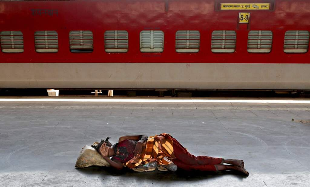 A homeless woman sleeps on a deserted platform of Lokmanya Tilak train terminus in Mumbai, as India's colossal railway system has come to a halt. (AP Photo/Rafiq Maqbool)