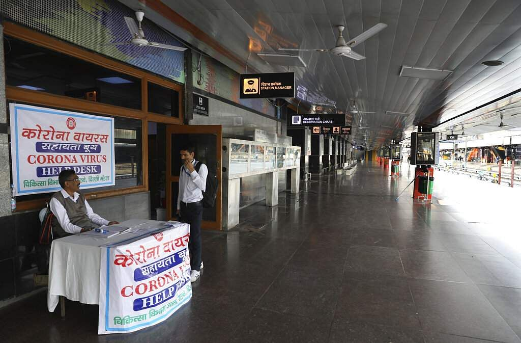 An Indian railways employee sits at a coronavirus help desk at the deserted New Delhi Railway station during the lockdown in the capital. (AP Photo/Manish Swarup)