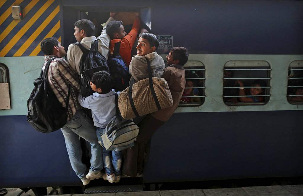 File photo: Passengers hang out from an overcrowded train to travel home for the Chhath Puja festival dedicated to the Sun God, at a railway station in New Delhi. (AP Photo/Kevin Frayer, File)