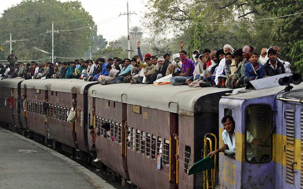 File photo: Hindu devotees sit on the roof of a train as they leave after attending Shivratri festival at Bhavnath temple in Junagadh from Ahmedabad. (AP Photo/Ajit Solanki, File)