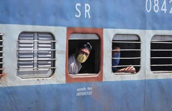 Passengers wearing masks look out from a train in Jammu. India's colossal railway system has come to a halt as officials take measures to keep the coronavirus from spreading. (AP Photo/Channi Anand)