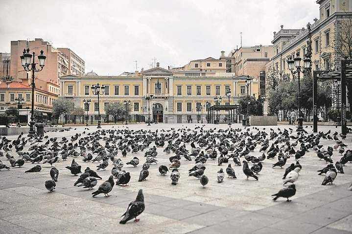 Athens, Attica, Greece: Pigeons search for food in an empty square in Athens. (AFP/Louisa Gouliamaki/Adem Altan)