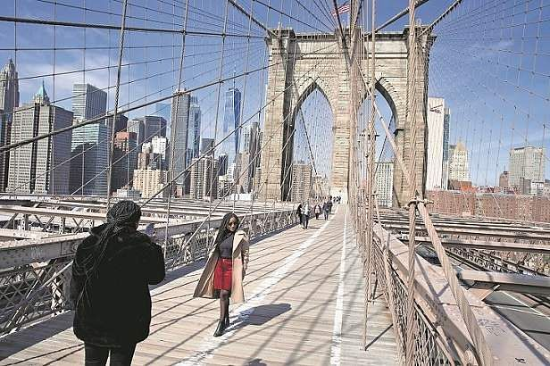 New York, US: A couple clicks a picture on the normally packed Brooklyn Bridge. (AP Photo/Mark Lennihan)