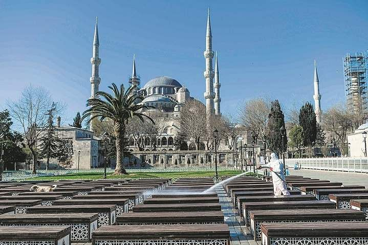 Istanbul, Turkey: A member of the Fatih Municipality disinfects Istanbul's Sultanahmet square with the Blue Mosque seen in the background. (AFP/Bulent Kilic)