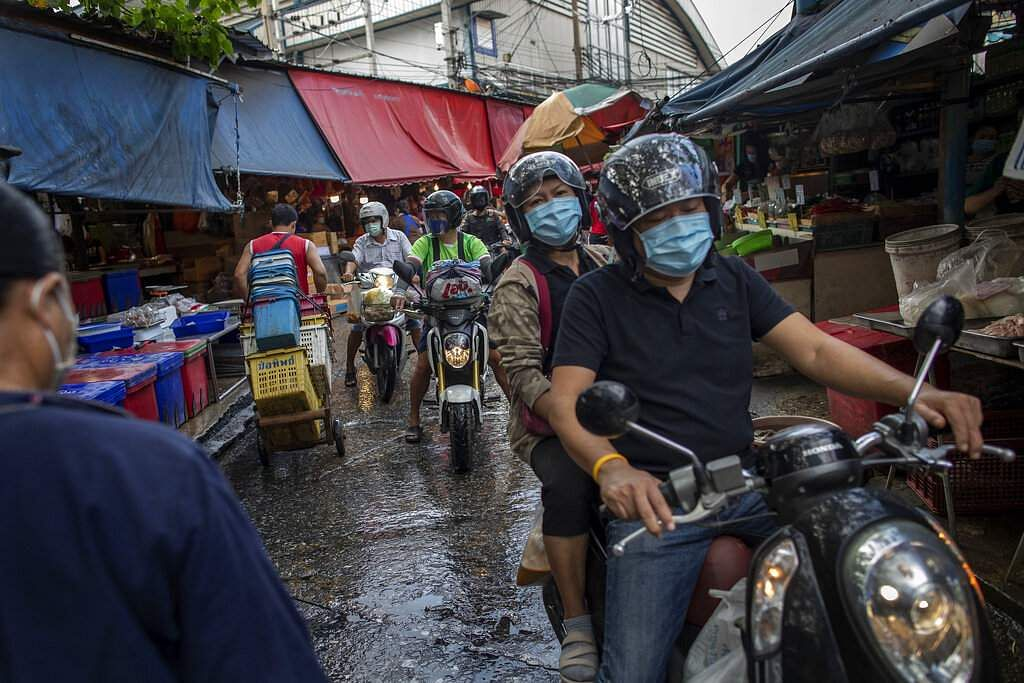Thai people wearing protective masks ride through a market in Bangkok, hours before Thailand's government declared an emergency to control the coronavirus outbreak. (AP Photo/Gemunu Amarasinghe)