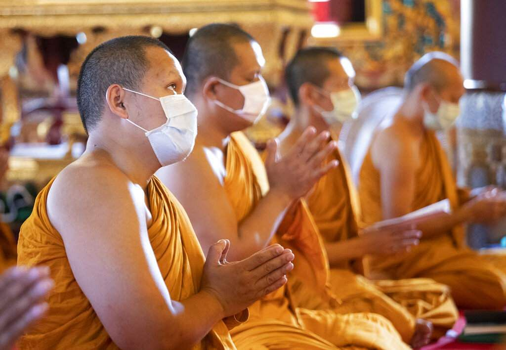 Buddhist monks wear face masks as they pray for good luck at the Debsirin Temple in Bangkok, Thailand. (AP Photo/Sakchai Lalit)
