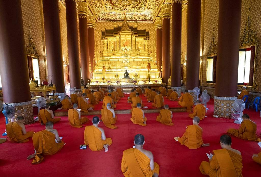 Buddhist monks wear face masks to protect themselves from the coronavirus as they pray for good luck at Debsirin Temple in Bangkok, Thailand. (AP Photo/Sakchai Lalit)
