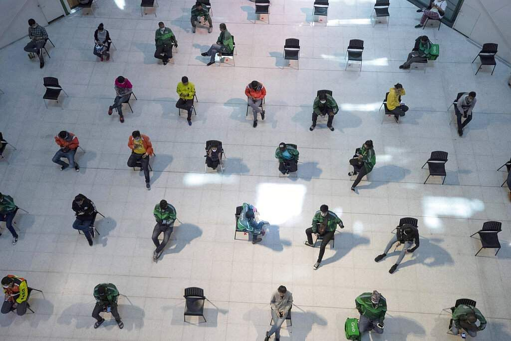People practice social distancing as they sit on chairs spread apart in a waiting area for take-away food orders at a shopping mall in Bangkok, Thailand. (AP Photo/Sakchai Lalit)