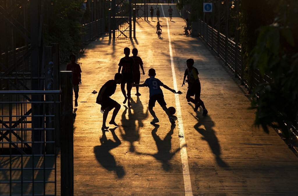 Children play soccer in the afternoon light in Bangkok, as Thailand's government announced a month-long state of emergency to control the coronavirus outbreak. (AP Photo/Gemunu Amarasinghe)