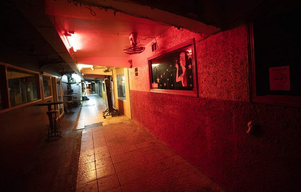 An empty line of closed bars stays lit in the entertainment district of Bangkok, as a month long state of emergency has been enforced in Thailand to control the coronavirus. (AP Photo/Sakchai Lalit)